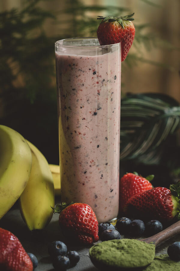 Beautiful fruit smoothie with fresh ingredients surrounding glass.