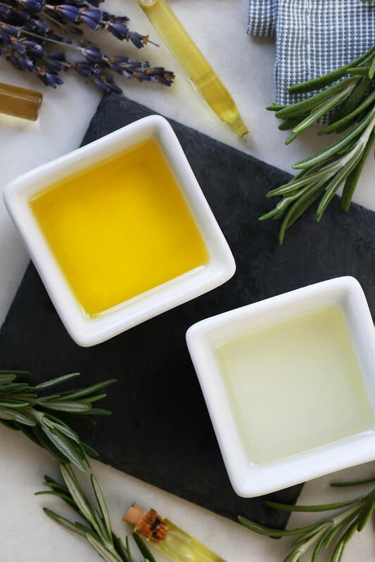Vibrant deep yellow jojoba oil and clear argan oil arranged with fresh rosemary and lavender flowers to be combined into a DIY hair moisturizer.