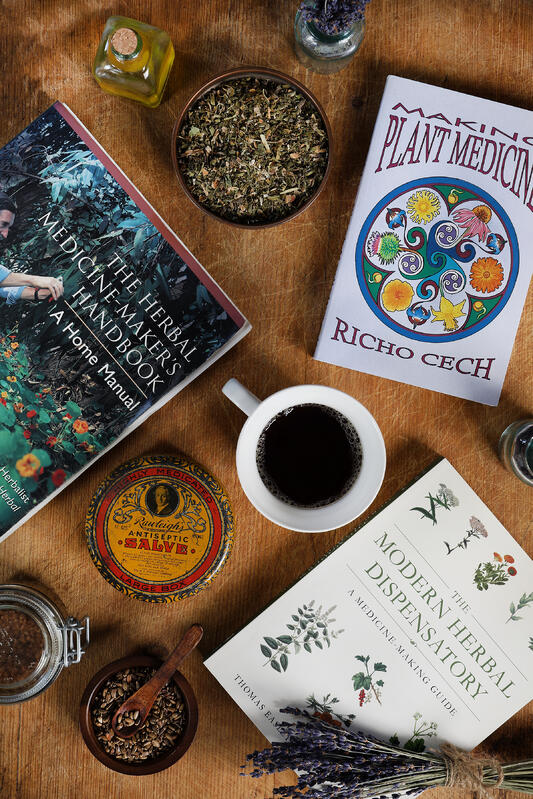 Several books about herbal medicine surrounded by herbs, a cup of tea and vintage props.