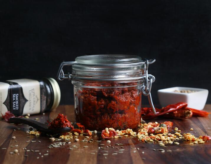 Pantry jar filled with red chili harissa paste sitting next to ingredients for the recipe