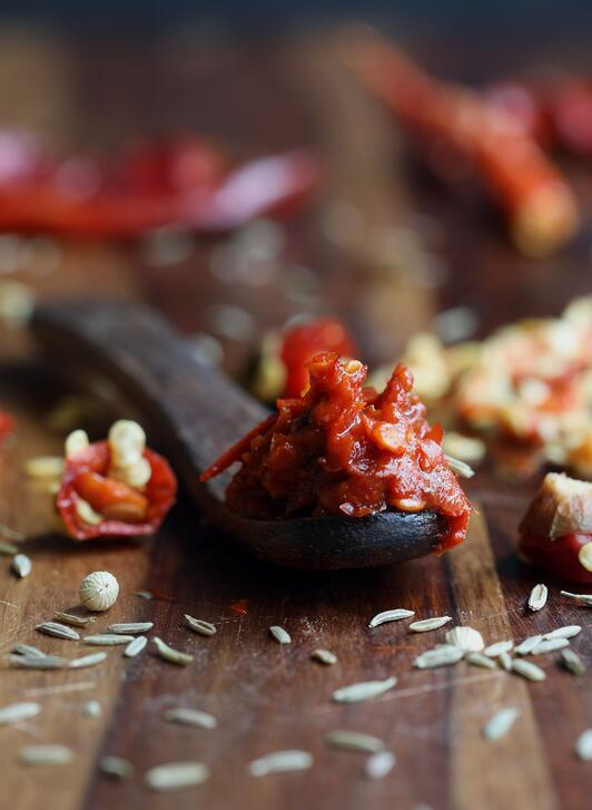 Wooden spoon showing fresh harissa paste made from rehydrated chili peppers