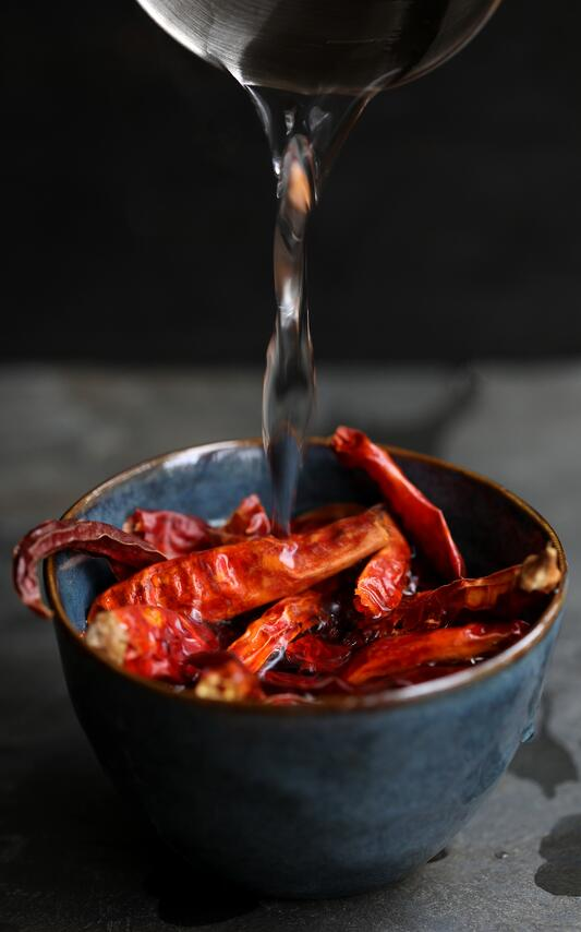 Hot water pouring over ceramic bowl with dried chilies in order to rehydrate them