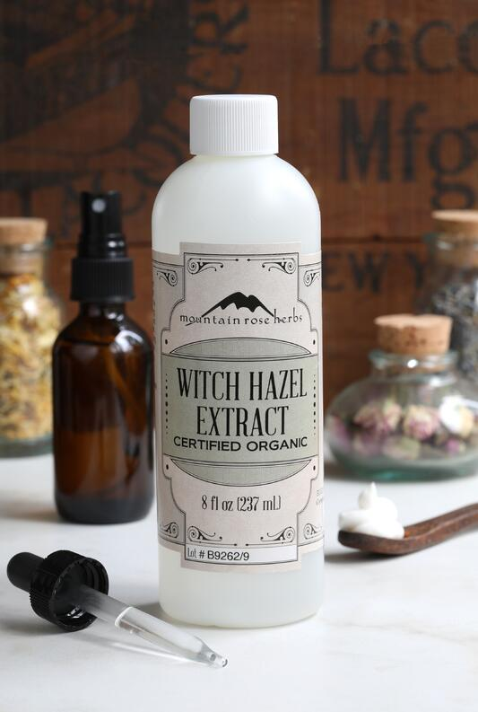 8 oz plastic bottle filled with Mountain Rose Herbs Organic Witch Hazel Extract surrounded by glass apothecary bottles