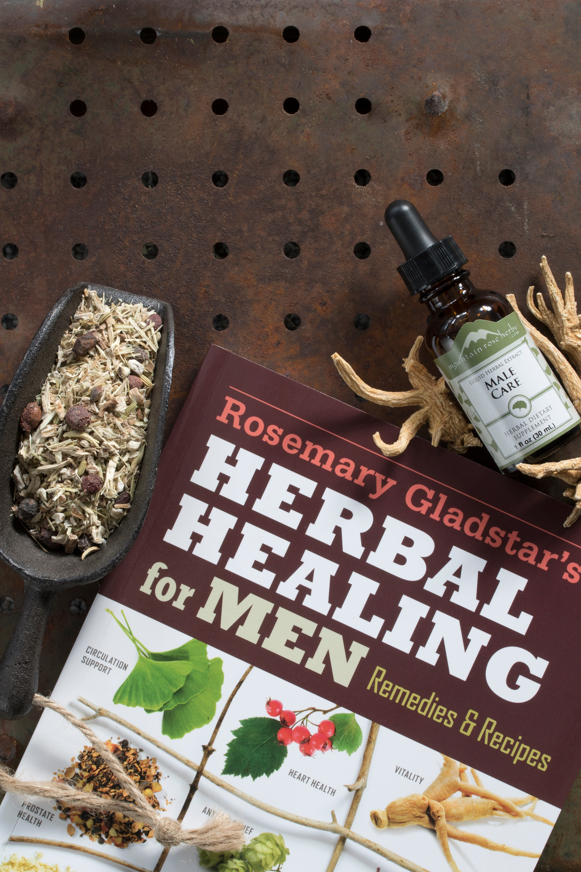Herbal Healing For Men book sitting on locker metal next to Male Care extract and other dried herbs