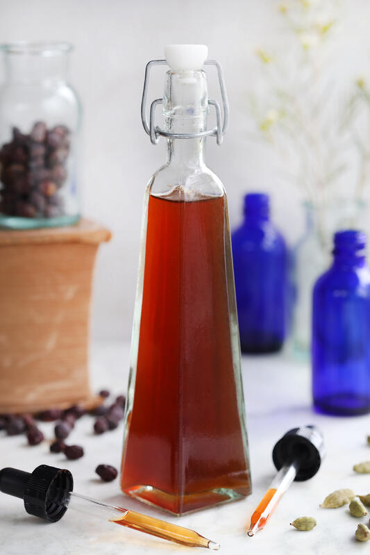 Unique shaped clear class bottle with rich red liquid surrounded by medicine droppers, dried berries and cardamom pods.