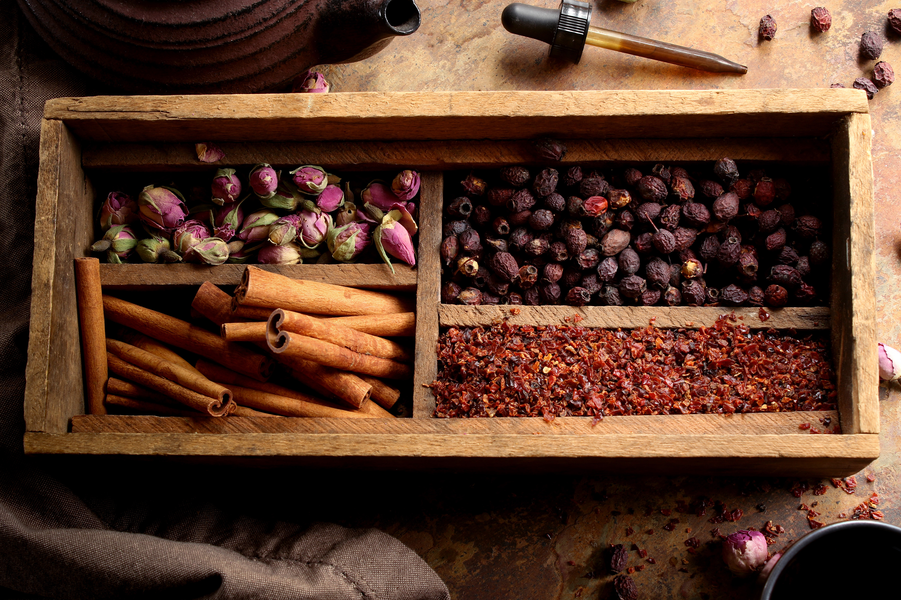 Various herbs for heartache or helping with the blues are arranged in a vintage wooden box. Herbs like rose buds, cinnamon, rosehips, and hawthorn are all helpful when tackling sadness or heartbreak.
