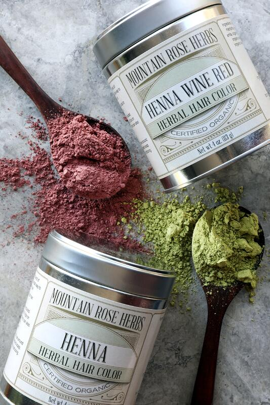 Two tins of Henna with spoons of red and green powder spilling out