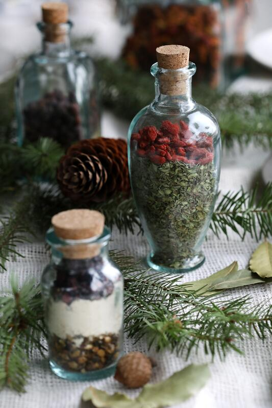Decorative bottles filled with colorful herbs displayed with holiday foliage.