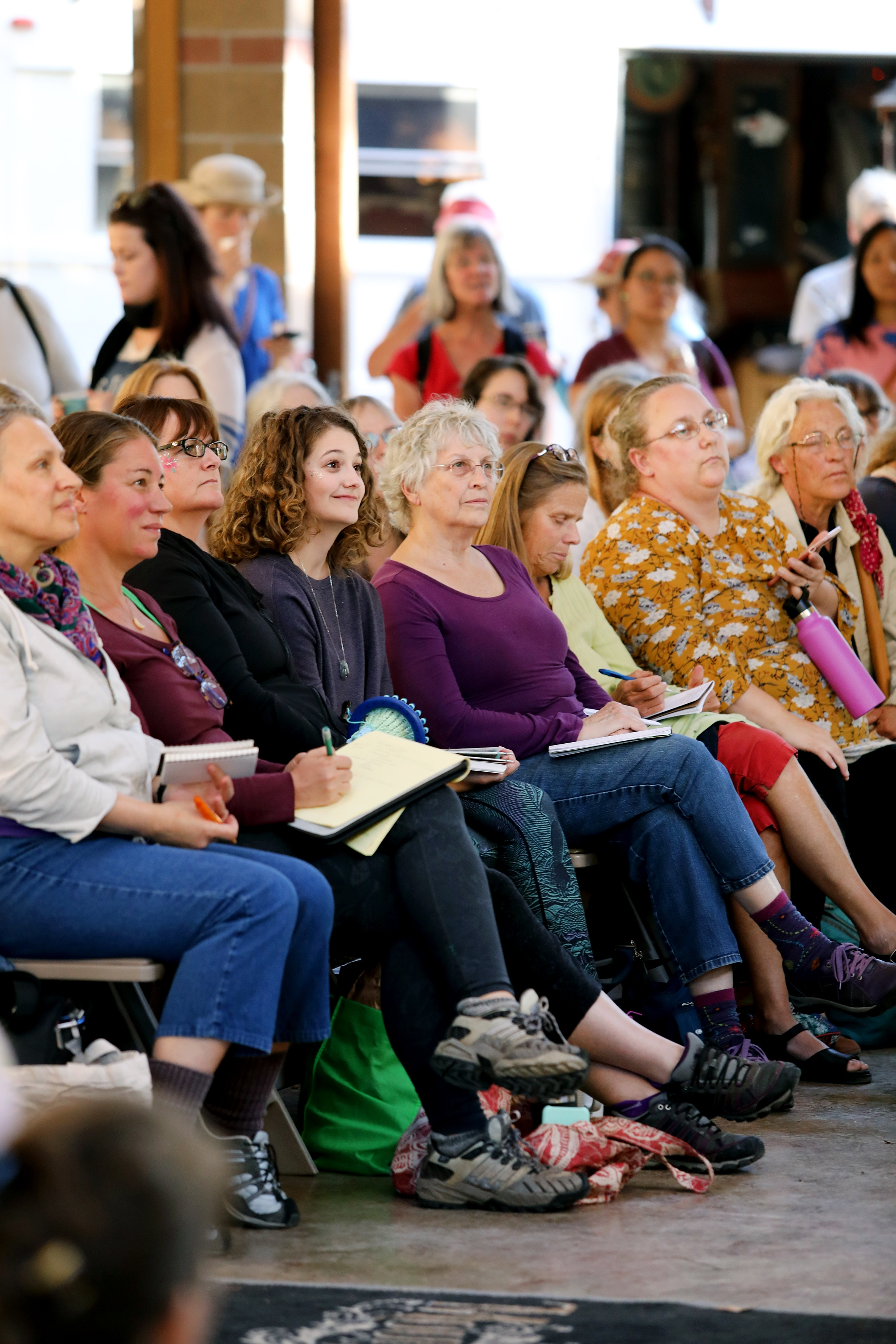 Group of people in varying age listening to a talk at the Mountain Rose Herbs Free Herbalism Project.