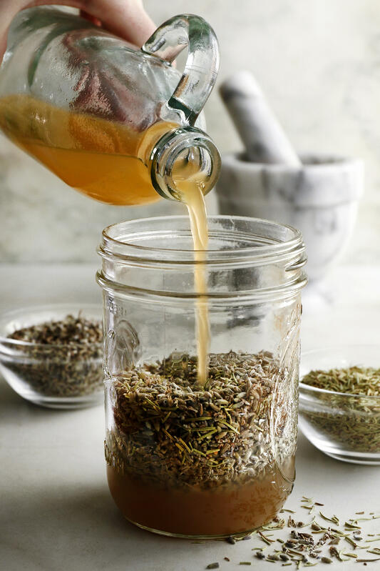 Pouring apple cider vinegar over lavender and rosemary herbs to create an infused herbal vinegar for cooking, cleaning, and skincare. A mason jar is full of herbs to be covered with apple cider vinegar for infusing.