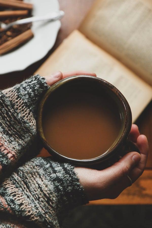 hands hold mug with warm beverage