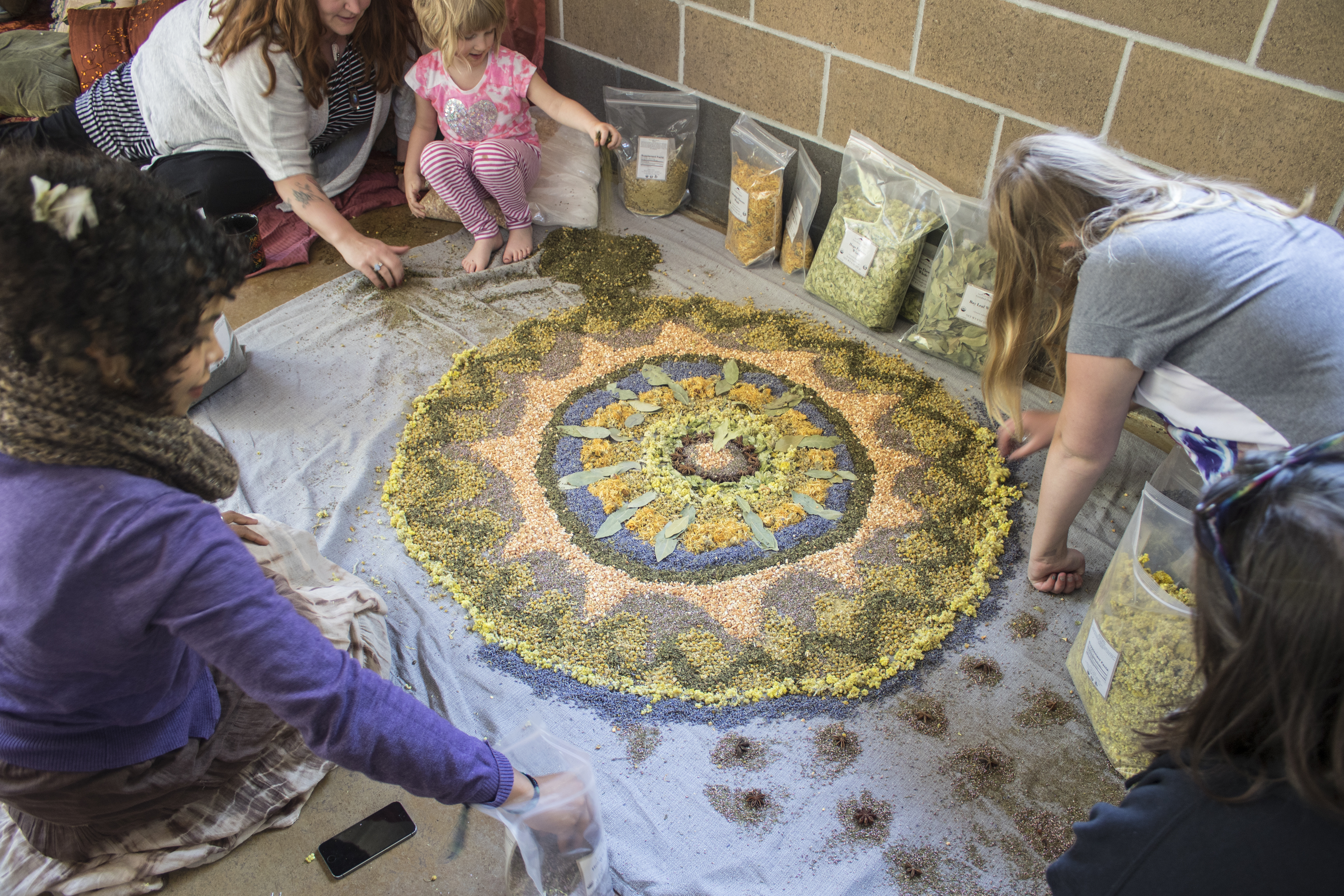 Group of people working on a mandala together with the use of botanicals.