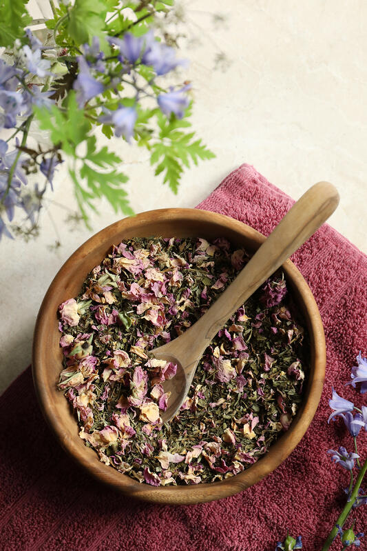 Peppermint, rose, and lemon balm herbal foot soak blend in wooden bowl with spoon.