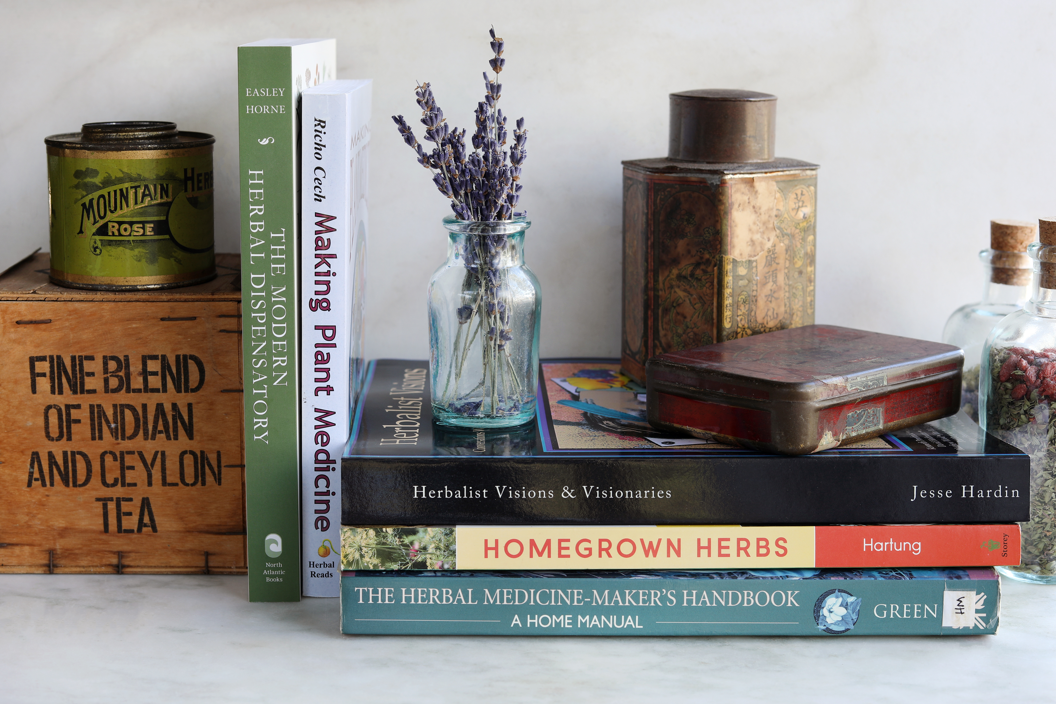 Stacks of herbal books with vintage props and fresh sprigs of lavender flowers