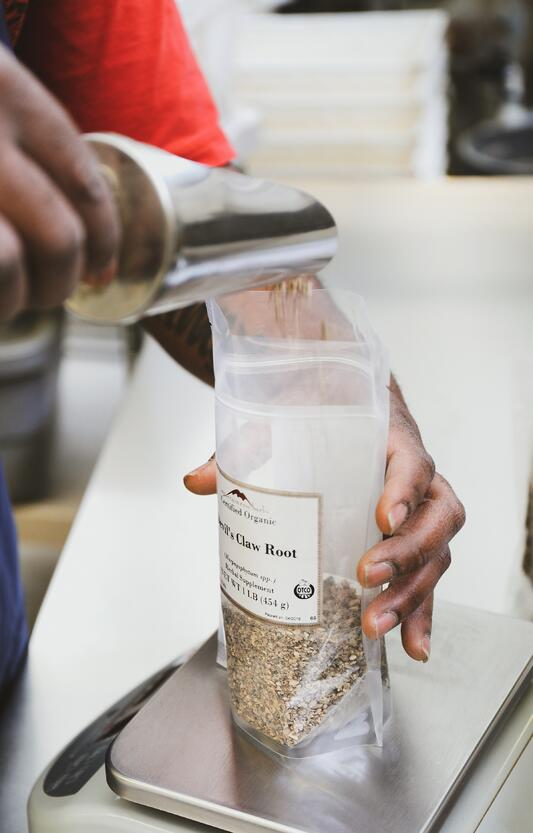 Hand using metal scoop to pour herbs into bag on scale