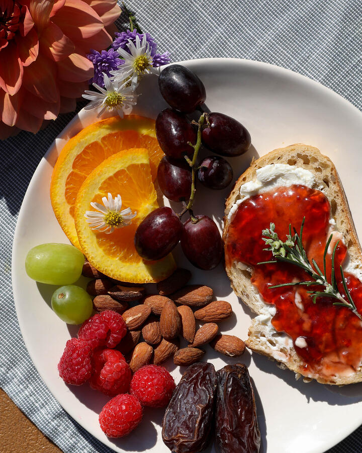 Hibiscus hot pepper jelly with cream cheese on baguette surrounded by fruit and nuts .