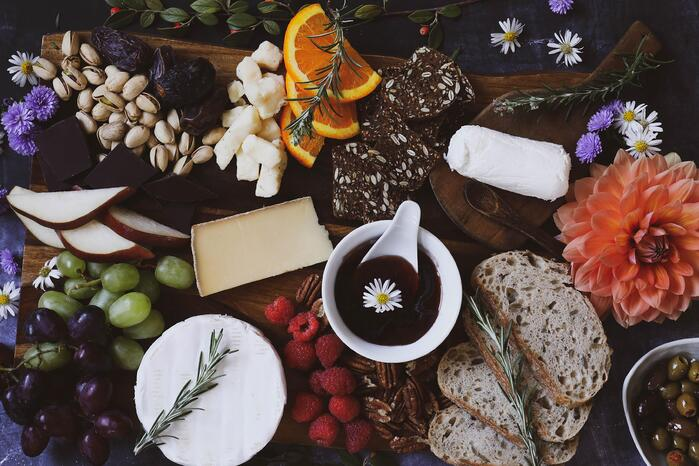 Appetizer platter with jam, cheese, bread and fruit