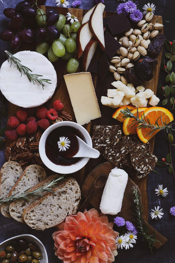 Cheese board with fruit, nuts, baguette, crackers, cheeses and hibiscus hot pepper jelly.
