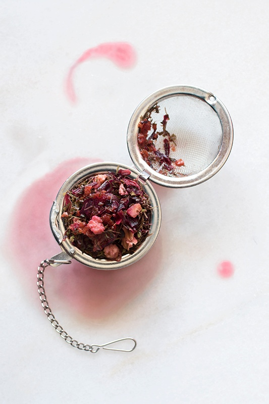 loose-leaf herbal tea made from hibiscus flowers and other herbs in a open strainer on a white counter