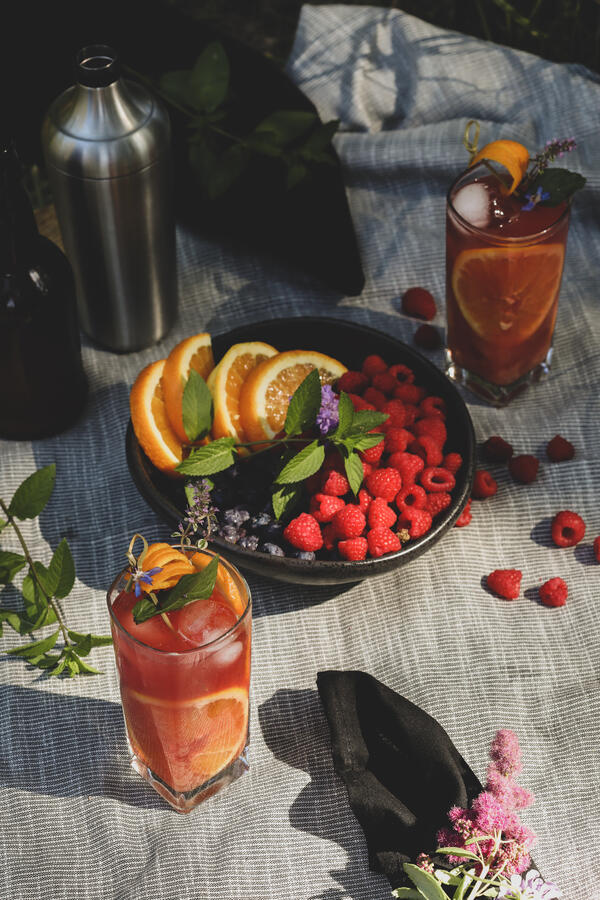 An herbal highball on a picnic blanket with fresh fruit.