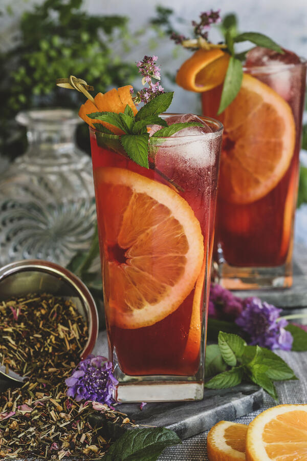 Summer Herbal Highballs in tall glasses garnished with mint and orange slices.