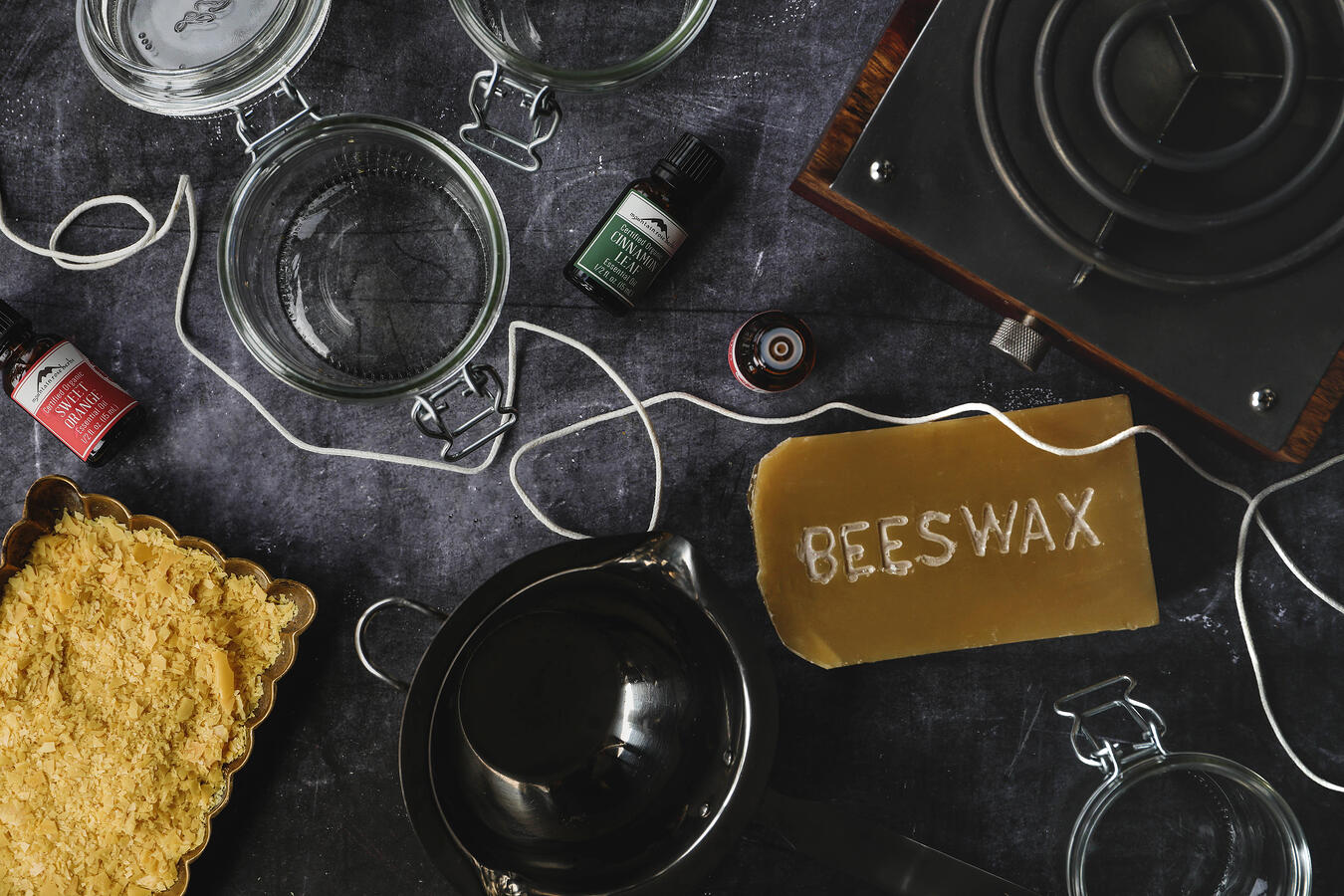 Beeswax, carnauba wax, essential oils, and other candle making supplies laid out on a table