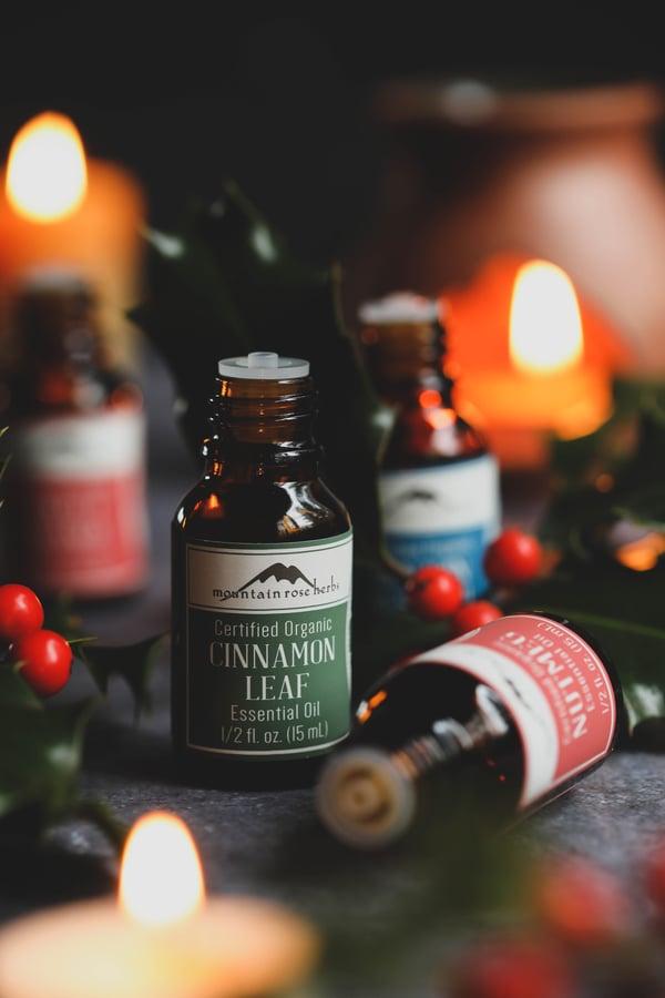 Sweet orange, cinnamon, and nutmeg essential oils in candlelight.
