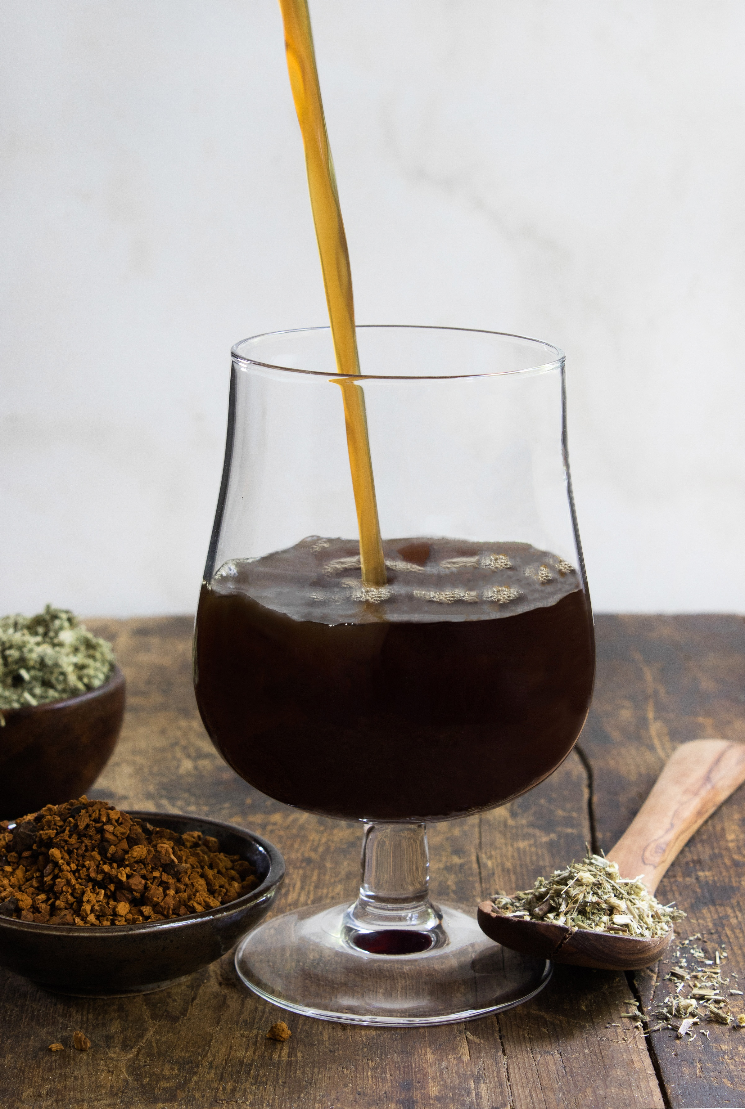 Deep roots gruit (herbal beer) being poured into a glass next to herbs and mushrooms used for brew