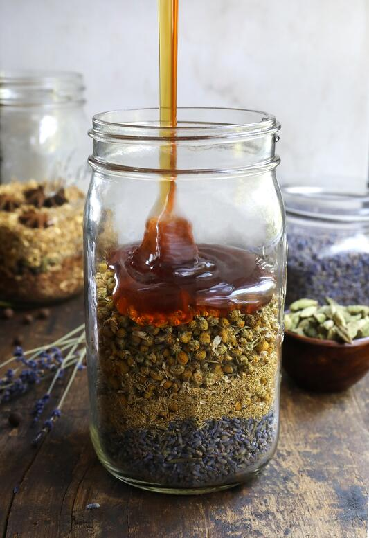 Pouring honey into mason jar filled with colorful dried herbs in it