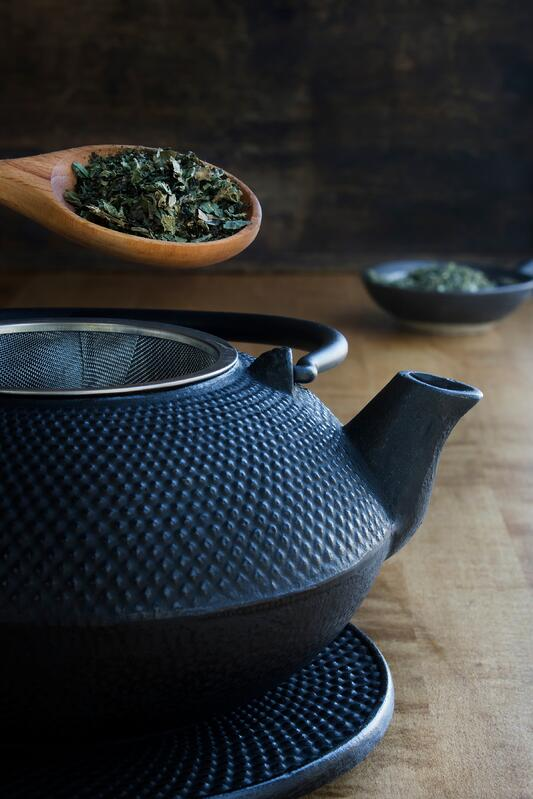Black cast iron tea pot being illed with green herbs on wooden table