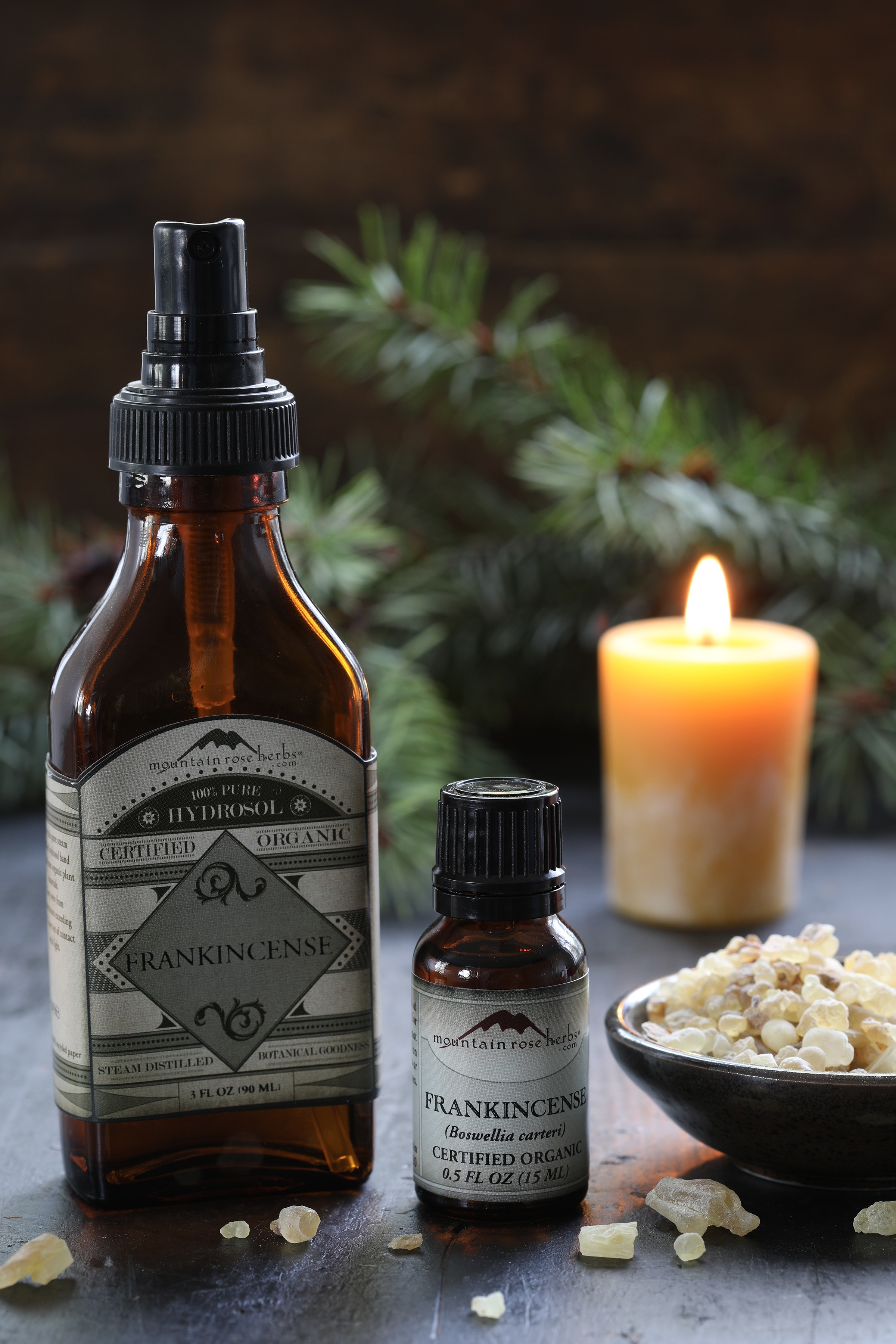 frankincense hydrosol and frankincense essential oil next to a bowl of frankincense resin with a candle in the background