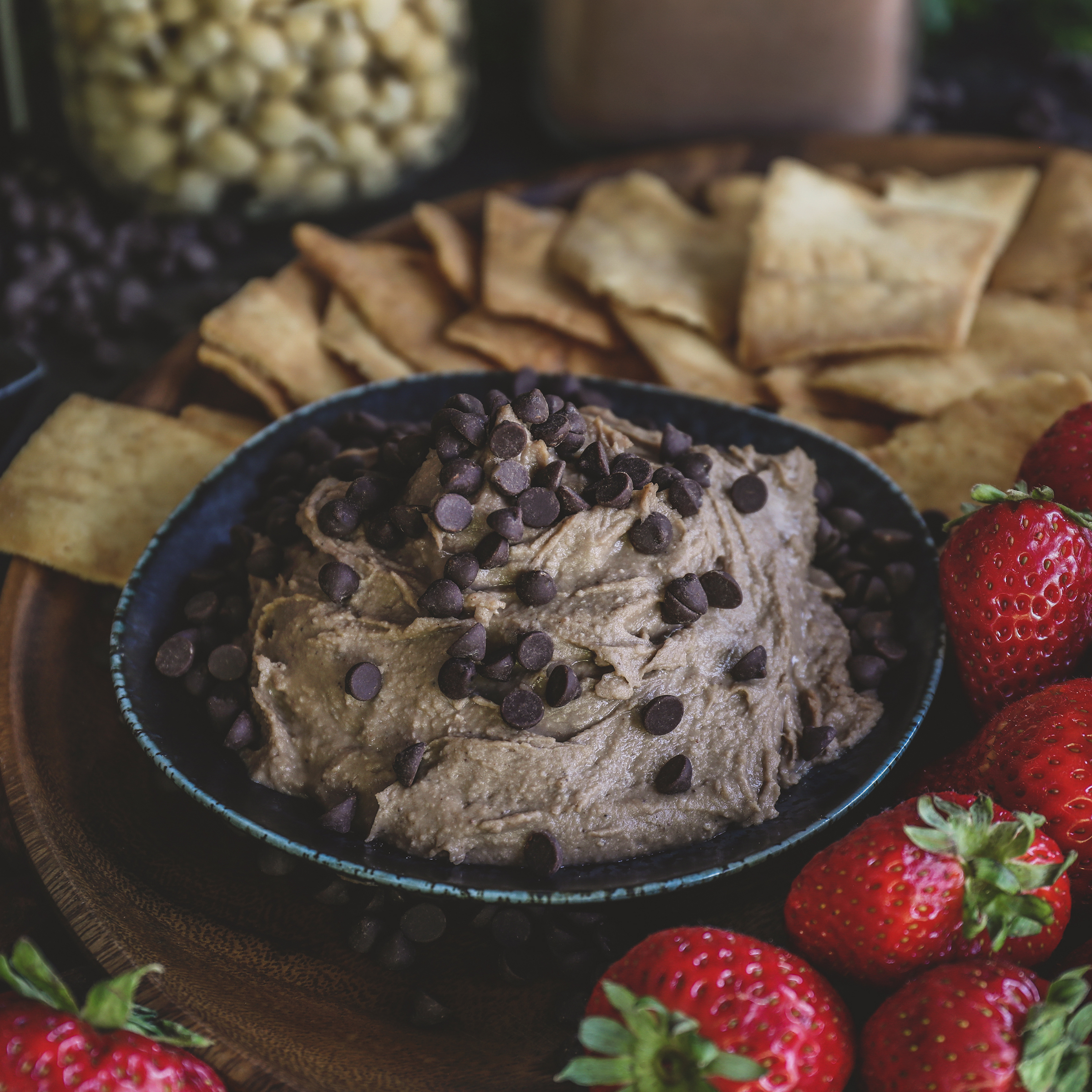 Bowl of chocolate hummus surrounded by pita crisps and strawberries.