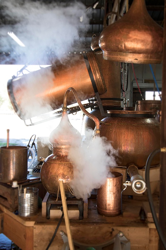 Copper stills with steam coming out of them