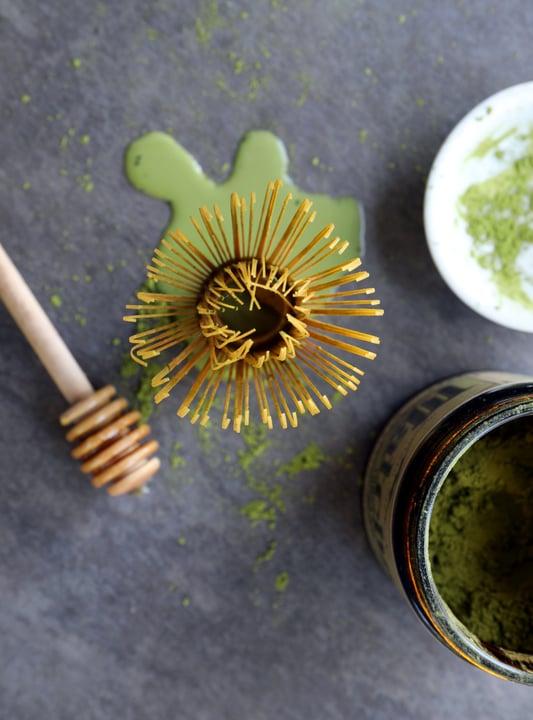 Matcha whisk facing upward towards ceiling near matcha powder and honey