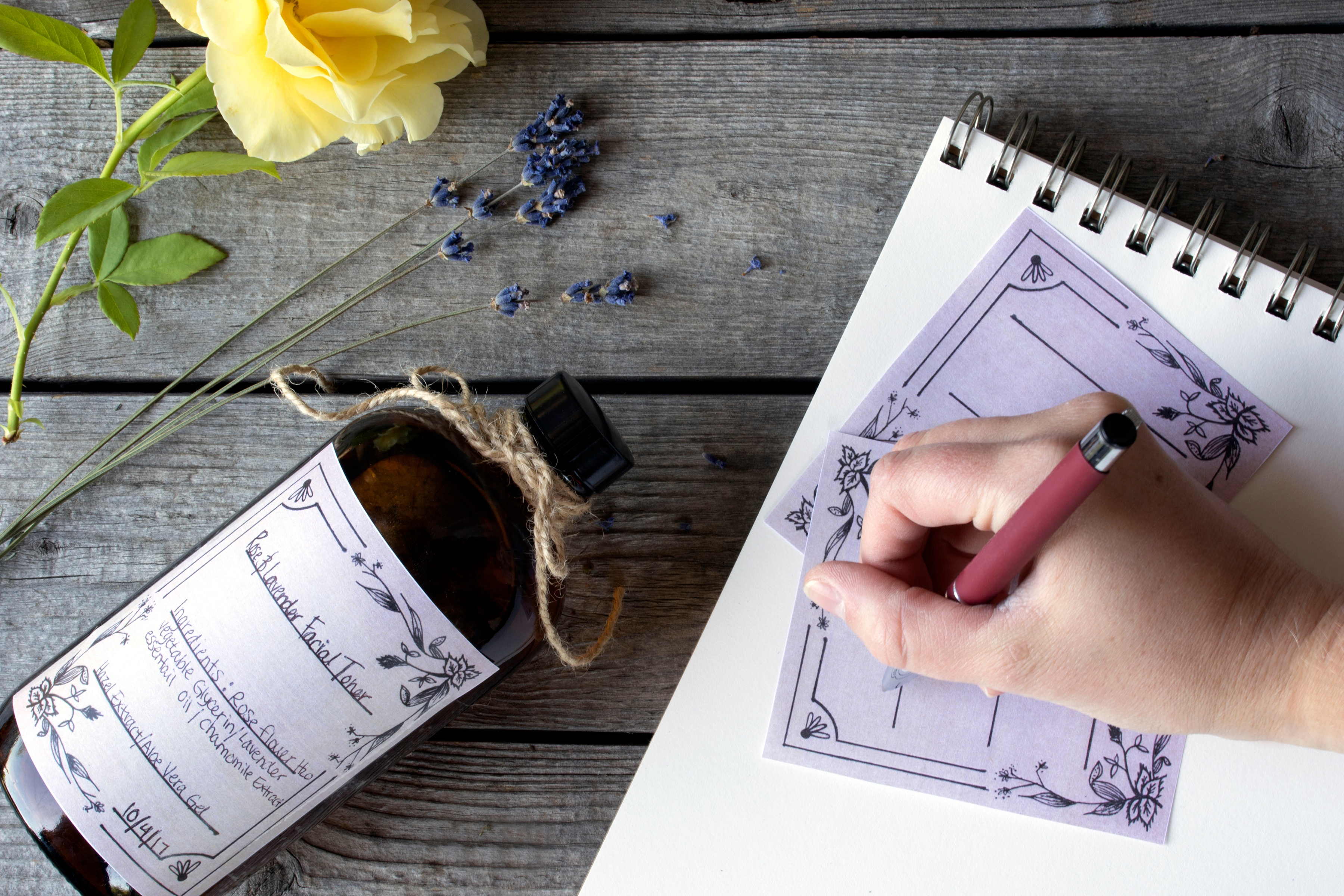 Person handwriting on a printed label with a yellow rose and lavender flowers on a wooden table.
