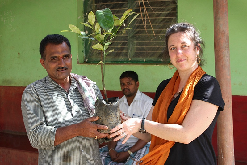 Indian farmer and COO from Mountain Rose Herbs holding sapling in front of a green building.