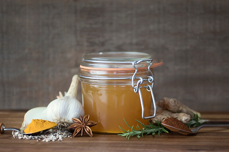 Homemade Fire Cider in glass jar surrounded by herbs and spices on table