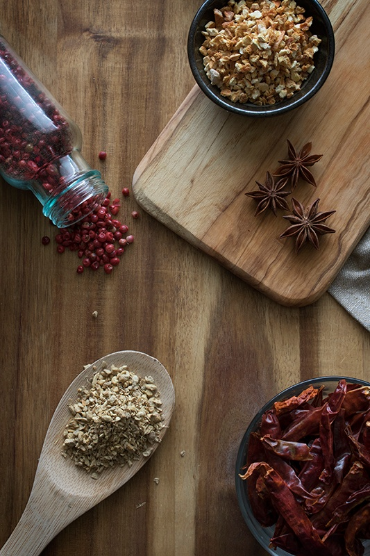 Fire Cider Ingredients including anise, peppercorns and peppers on wooden plank