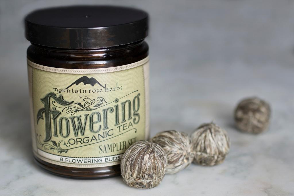 Organic flowering tea sampler jar and tea buds laying on counter