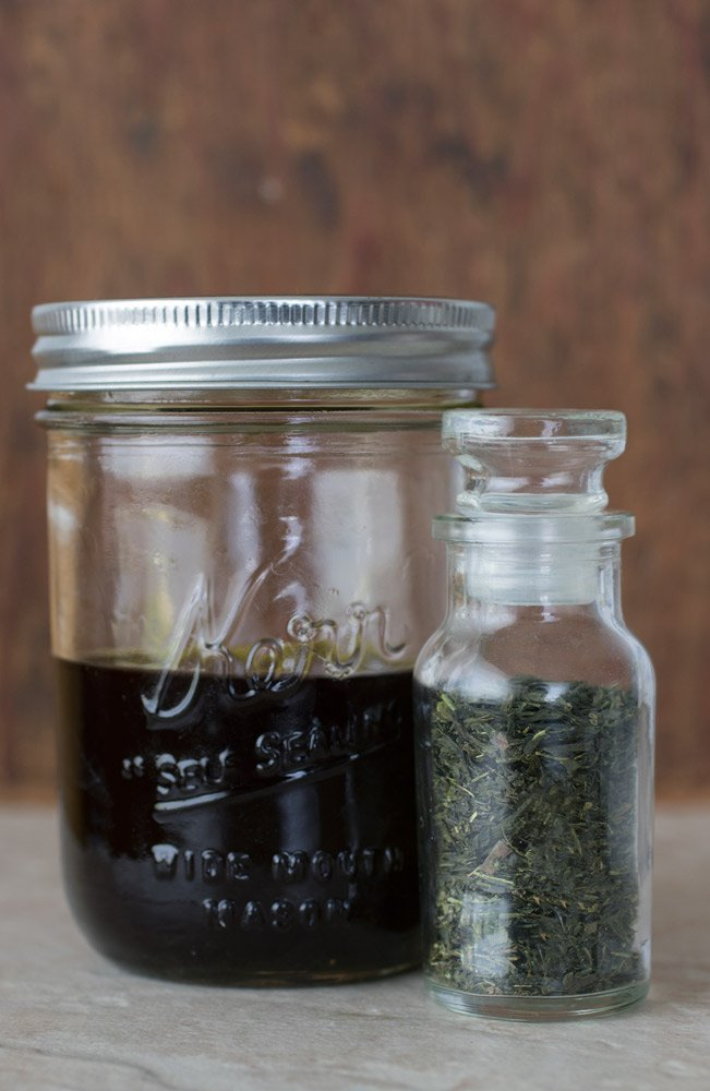 Green tea serum in a pint jar sitting beside a jar of green tea