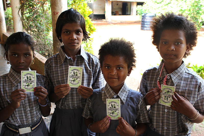 Children from rural Indian village in new school uniforms holding Mountain Rose Herbs stickers.