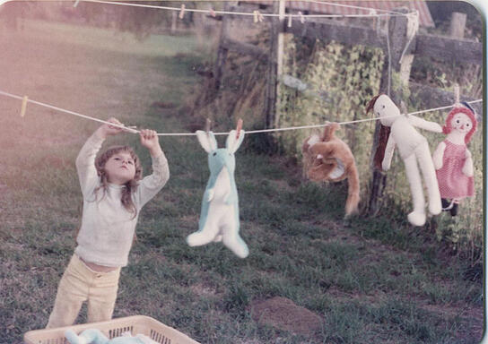 Girl Hanging Stuffed Animals on Clothes Line