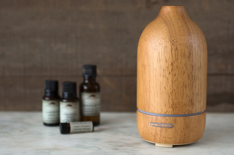 Natural wood ultrasonic diffuser with essential oils on counter