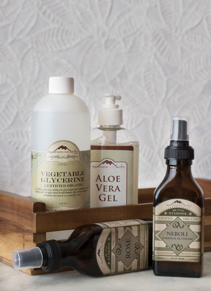 Ingredients for DIY body care including aloe vera gel and organic hydrosols on a tabletop