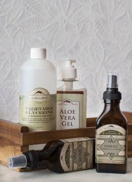 Los ingredientes para el cuidado corporal DIY incluyen el gel de aloe vera y los hidrosoles orgánicos en una mesa