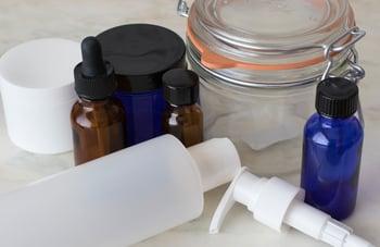 Los envases de plástico blanco y vidrio cobalto para el cuidado corporal DIY
