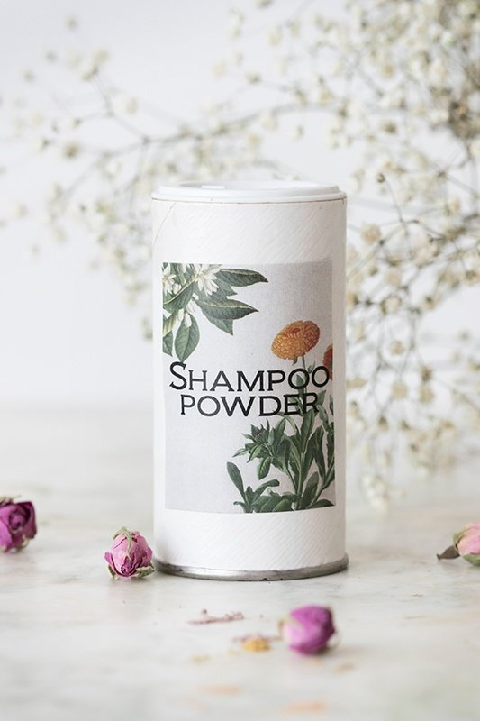 Shaker full of homemade dry shampoo powder surrounded by rose buds