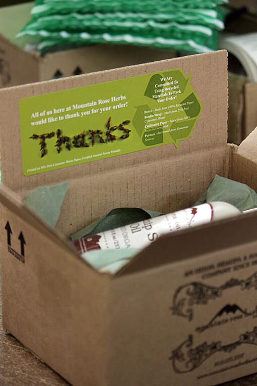 Cardboard box with Mountain Rose Herbs merchandise in it and a green eco-friendly sticker and green packaging