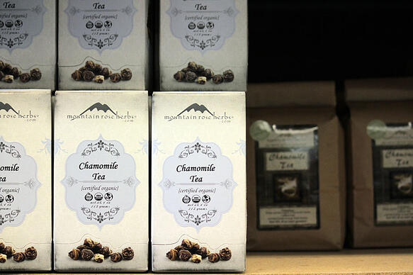 Boxes of organic chamomile tea stacked on shelf in shipping warehouse in Mountain Rose Herbs