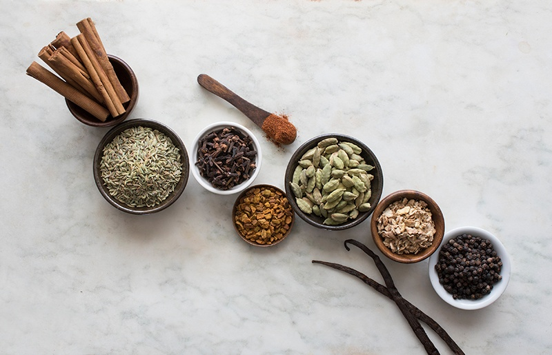 Herbs and spices in bowls on counter with an overhead view